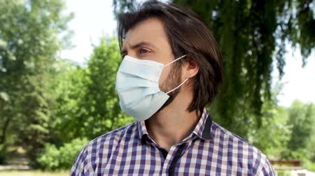 zsebkendő : Guy is standing in park and wearing mask on face he is sick and looking to left and right few times in a row. Stock mozgókép