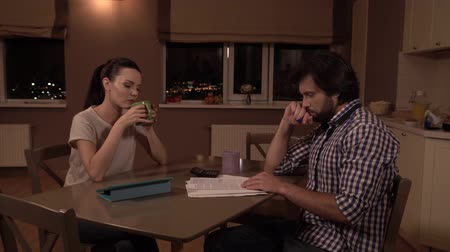 трепет : Upset man and woman sit on the table.  Girl drinks from cup and looks at husband. Стоковые видеозаписи