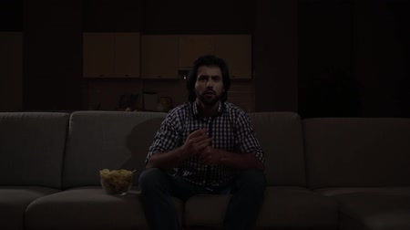 watch tv : Man sits on sofa and cheers watching TV.He holds remote control in hands. Stock Footage