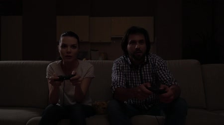fatality : Young couple enjoying playing game.Woman starts to cheering. Guy is frustrated.