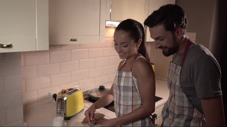 built up : Guy stands behind girl and holds hands on hers. She is lubricating chocolate on toast. Stock Footage