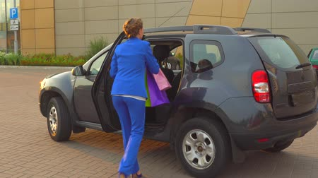 koszyk zakupy : Business woman in blue suit comes to car and opens back door,put on seat bags she got from shopping.