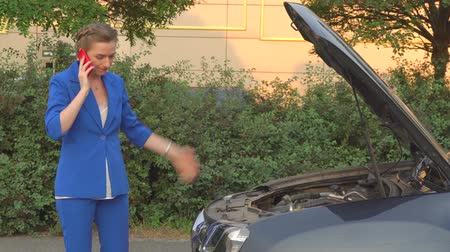 suite : Girl in blue suit stands in front of broken car and talks on phone.  Woman is calling about help. Stock Footage