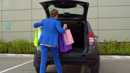 koszyk zakupy : Woman in blue suit open the trunk and puts colorful shopping bags in it.