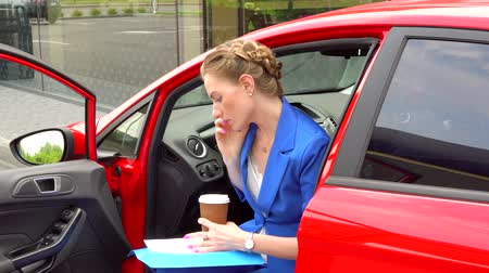 suite : Business woman sits in car and talkes on phone. Also she holds papers and cup with coffee. Girl talkes on phone. She points on paper and drinks coffee.