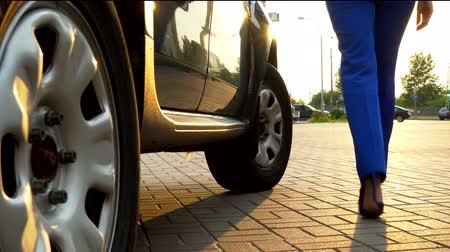 street market : Girl stands on ground from car and close its door. She wears blue suit and high heels. Woman walks away from car. Stock Footage