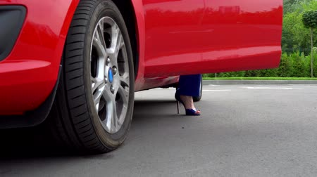 samochód : Girl openes front door of red car and puts on ground her legs. She stands up and close the door. Wideo