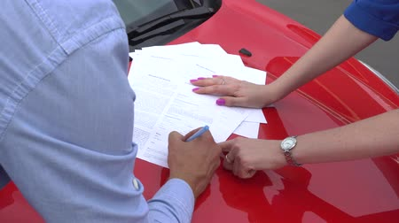 finom : Documents are lying on hood af red car. Girl points on two places for sigh. Guy puts there his sigh.