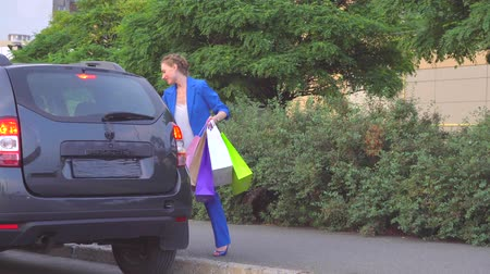 koszyk zakupy : Happy woman stands and holds shopping bags. She smiles. Girl waves with hand. Wideo