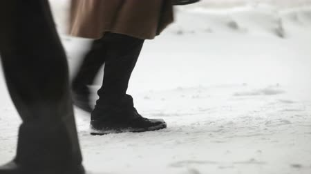 rüzgârla oluşan kar yığını : Cold winter weather. People walk on a snow-covered sidewalk in the city Stok Video