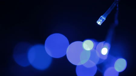 привело : Blue LED (light emitting diodes) lights garland sways in the wind on black background