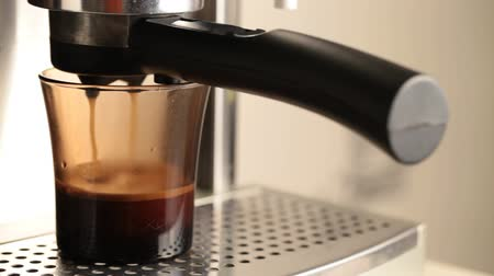 morning : Coffee pours in dark glass cup in espresso coffee machine