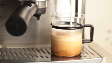 keverék : Coffee maker pouring hot milk foam in espresso to prepare coffee with milk Stock mozgókép