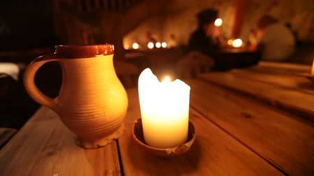 Észtország : Burning candle and clay cup on a wooden table in old restaurant of Tallinn, Estonia