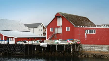 küçük sandal : Traditional Norwegian fishing village scene. Red wooden houses and packed fishing nets lies on the coast