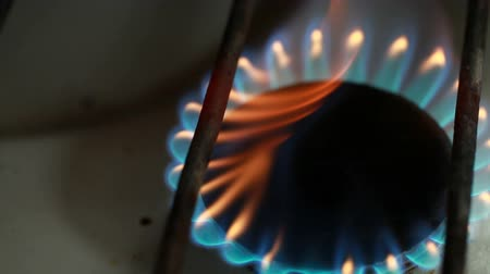 Old domestic gas ring stove burns with blue and orange flame