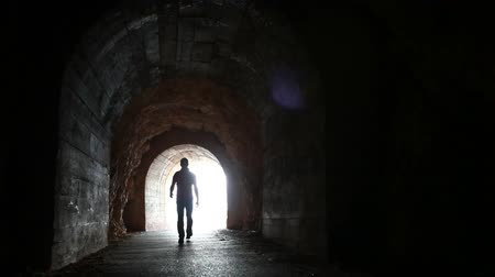 konec : Man goes through the dark concrete tunnel into the glowing end Dostupné videozáznamy