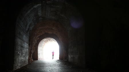 прихожая : Man runs into the dark concrete tunnel from the glowing end