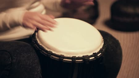 Woman plays fast beat on djembe, traditional African drum