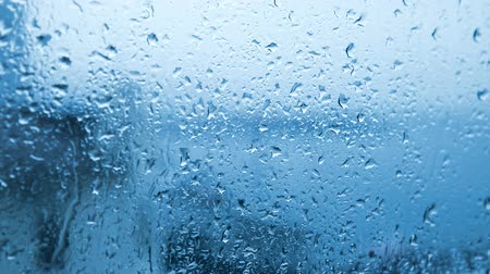 Blue rainy background with flowing down water drops on window glass Stock mozgókép