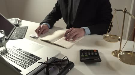 spravedlnost : justice and law concept.businessman or lawyer or accountant working on accounts using a calculator and laptop computer and documents in 4k (UHD) Dostupné videozáznamy