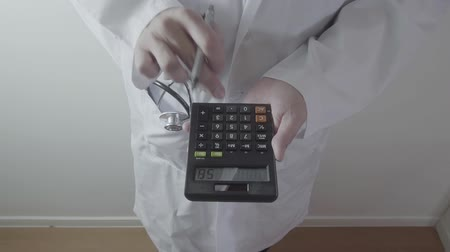 expenditure : Healthcare costs and fees concept.Hand of smart doctor used a calculator for medical costs in modern hospital
