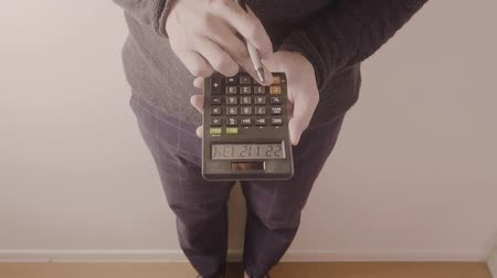 young designer or businessman working with calculator in modern office in slow motion