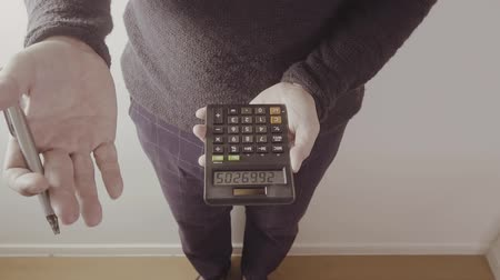 вычислять : young designer or businessman working with calculator in modern office in slow motion