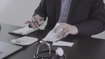 heart monitor : Healthcare costs and fees concept. Hand of smart doctor used a calculator for medical costs in modern hospital in slow motion, Slog Stock Footage