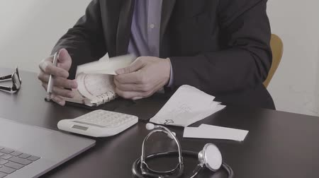 醫療保健 : Healthcare costs and fees concept. Hand of smart doctor used a calculator for medical costs in modern hospital in slow motion, Slog 影像素材