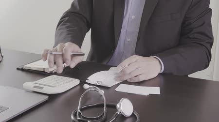 поставщик : Healthcare costs and fees concept. Hand of smart doctor used a calculator for medical costs in modern hospital in slow motion, Slog Стоковые видеозаписи