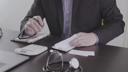 gondoskodó : Healthcare costs and fees concept. Hand of smart doctor used a calculator for medical costs in modern hospital in slow motion, Slog Stock mozgókép