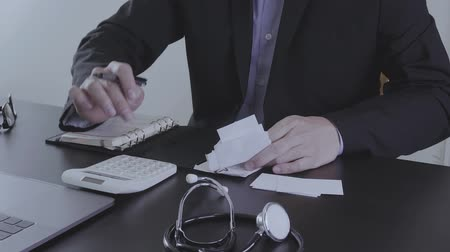 ücret : Healthcare costs and fees concept. Hand of smart doctor used a calculator for medical costs in modern hospital in slow motion, Slog Stok Video