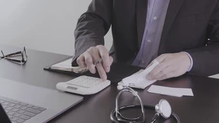 charges : Healthcare costs and fees concept.Hand of smart doctor used a calculator for medical costs Stock Footage