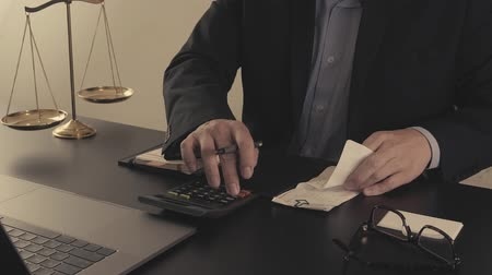 bookkeeping : Justice and law concept.Businessman or lawyer in the office working with calculator