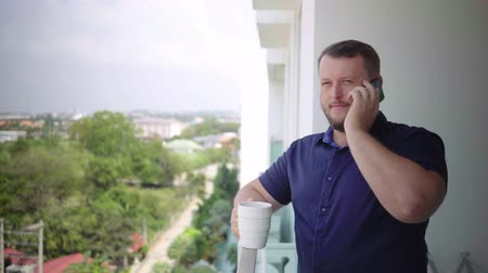 man on the balcony drinking with a mug and talking on the phone Dostupné videozáznamy