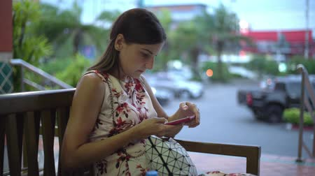 Woman gets message and takes phone to read it smiling close up 4k. Dostupné videozáznamy