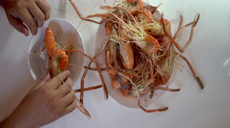 seafood recipe : man in a seafood store putting boiled shrimp on a plate. Shooting close-up