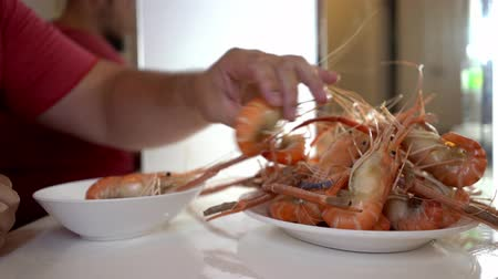 man in a seafood store putting boiled shrimp on a plate. Shooting close-up