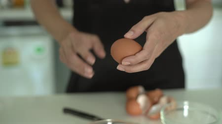 separado : Break egg. Cooking food. Baking ingredients, breaking the eggs, separating yolk from protein. Glass bowl for kneading. Fresh organic eggs falling into bowl. Preparing ingredients. Stock Footage