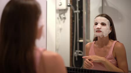 The girl put a mask on the face at home. The concept of beauty.