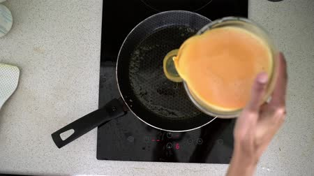 women pour mixed milk and eggs to pan for preparing omelet for breakfast.