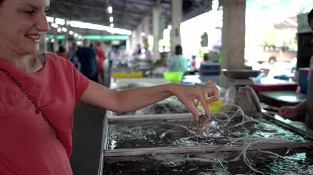 woman chooses shrimp on the market. female surprised big shrimp.