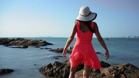 The girl walks on the rocks by the sea. Ease, enjoyment.