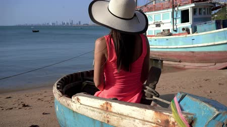 思考 : Beautiful girl with long hair sitting on an old tramp boat in the fields. 動画素材