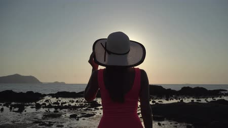 wistful : girl in a hat strolls along the beach at sunset.