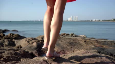 female legs walking on the rocks by the sea on a sunny day. Dostupné videozáznamy