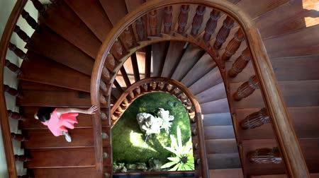 ctižádost : female in a pink dress comes down and climbs a round staircase with greenery and a fountain. 4k.