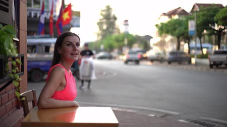поздний завтрак : Female is waiting for someone in a cafe on the street of the meeting, waving her hand to a friend, 4k.
