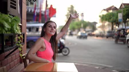 sofisticado : Female is waiting for someone in a cafe on the street of the meeting, waving her hand to a friend, 4k.